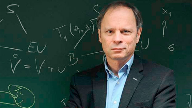 Photo of Jean Tirole standing in front of a blackboard full of equations